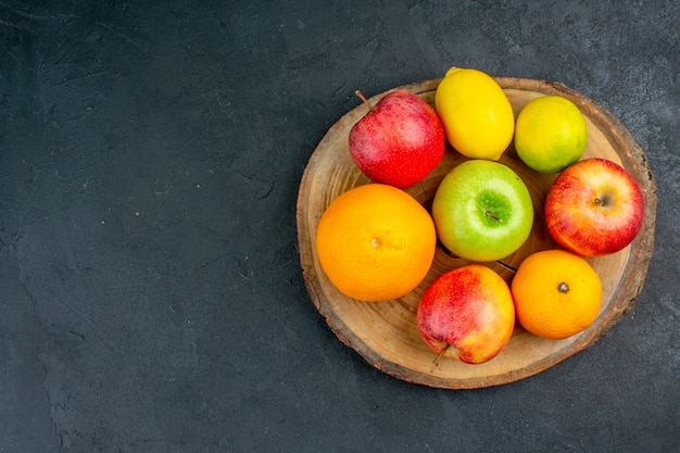 Vista dall'alto mele limone arance su tavola di legno su superficie scura con copia spazio