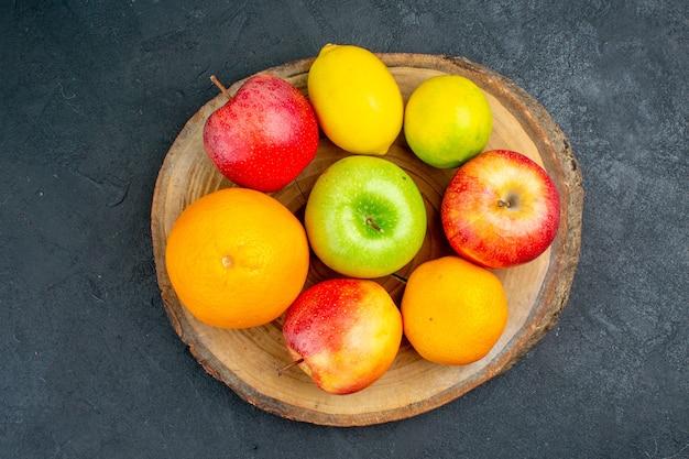Top view apples lemon oranges on wood board on dark surface