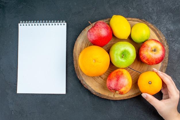 Top view apples lemon oranges on wood board notebook orange in woman hand on dark surface