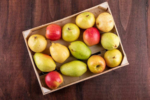 Top view apples and pears in crate on brown wooden  horizontal