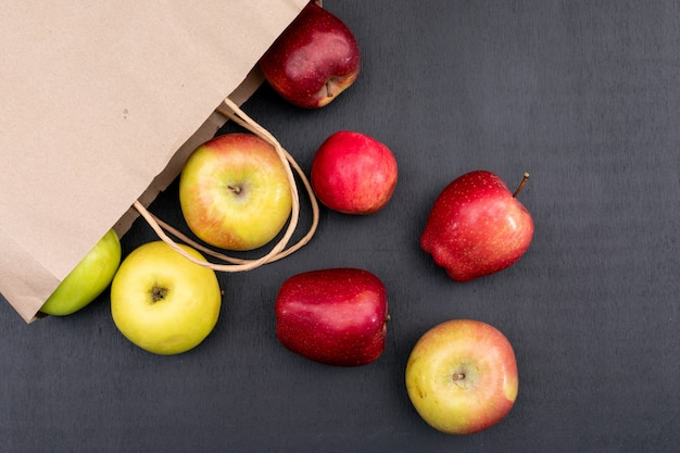 Top view apples with beige paper bag on black  horizontal