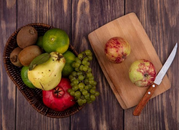 Вид сверху яблоки с ножом на разделочной доске с виноградом, мандаринами, грушей и гранатом в корзине на деревянной стене