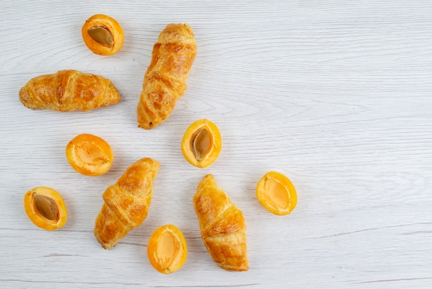 A top view apricot croissants with fresh apricots on the white desk fruit cake