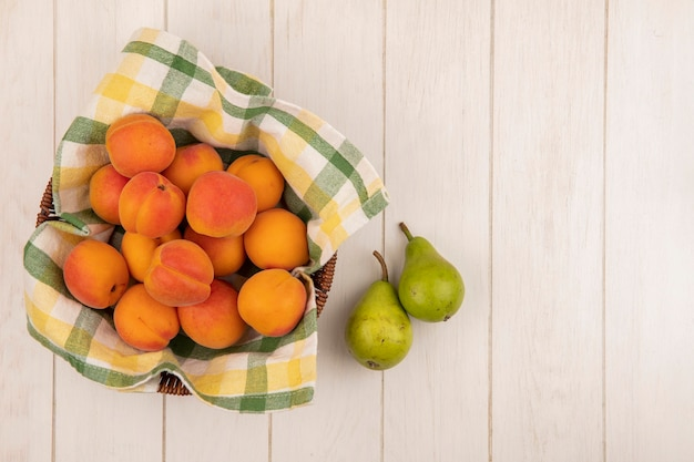 Top view of apricots in basket with pears on wooden background with copy space