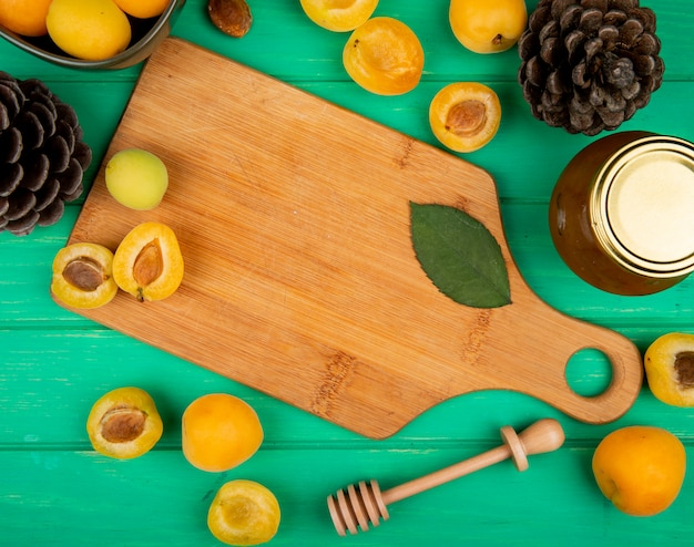 Top view of apricots and leave on cutting board with pinecones and peach jam on green background