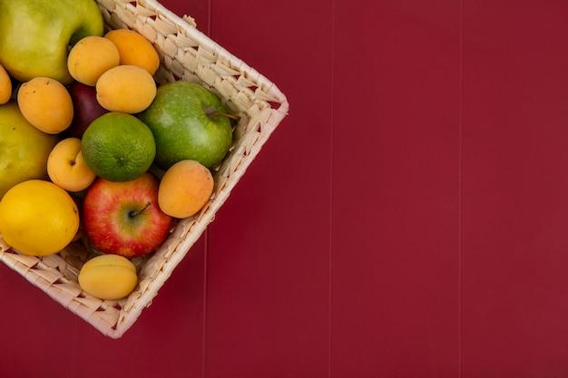 Vista dall'alto di albicocche con mele in un cesto su una superficie rossa
