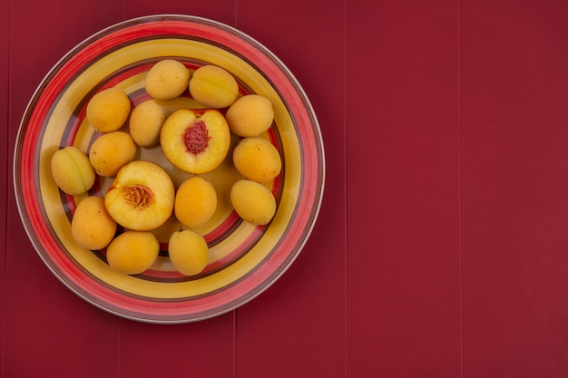 Top view of apricots with peach on a plate on a red surface