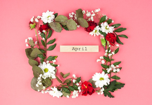 Top view of april text middle of colorful flower wreath against peach surface