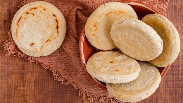 Top view of arepas in bowl with cloth