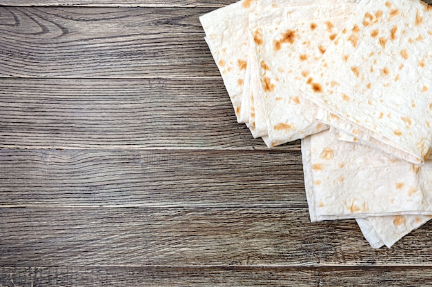 Top view armenian flat think pita bread on wooden background with copy space