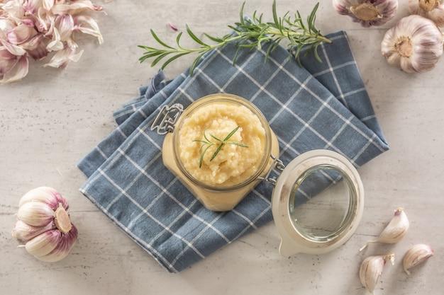 球根と皮をむいたクローブとローズマリーが付いている素朴な台所の布の上に置かれたガラスの瓶の中の上面の芳香のニンニクペースト。
