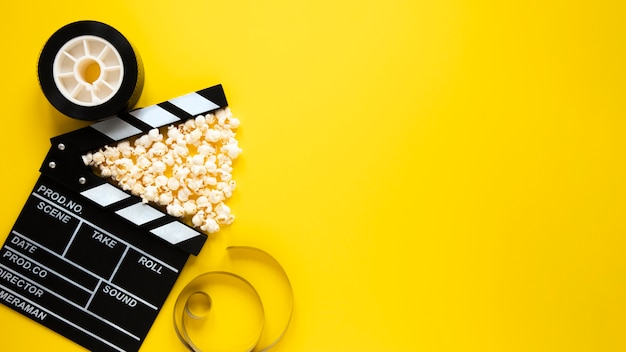 Top view arrangement of cinema elements on yellow background with copy space