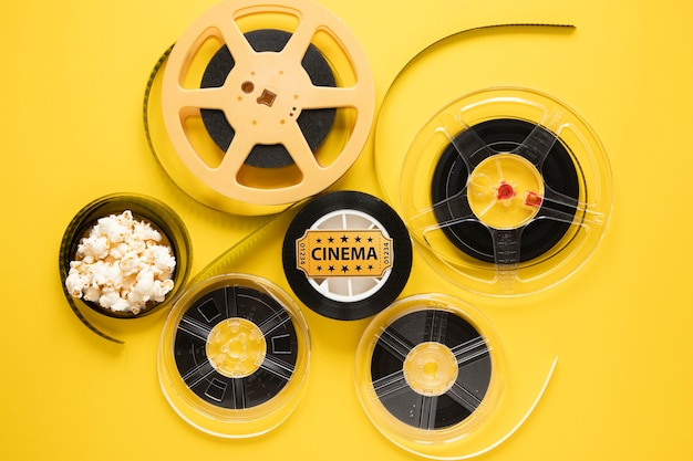 Top view arrangement of cinema elements on yellow background