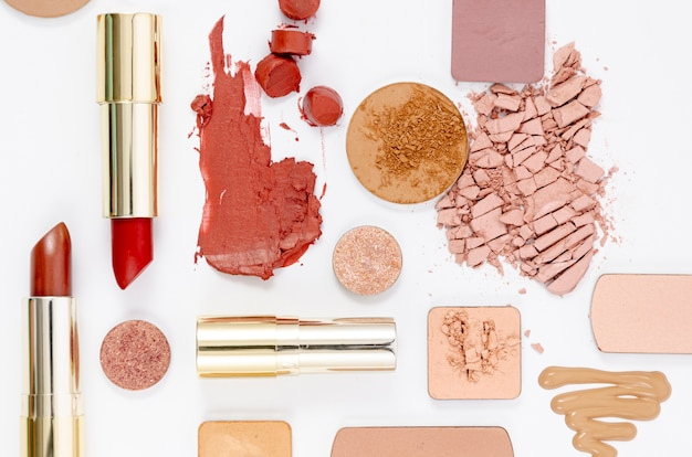Top view arrangement of colorful cosmetics on white background
