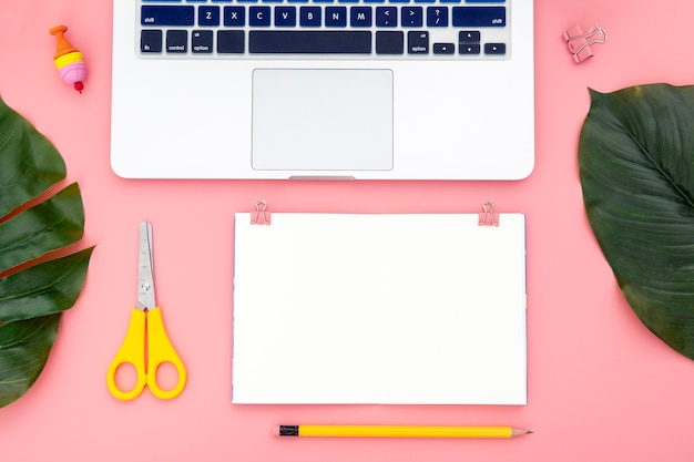 Top view arrangement of desk elements on pink background