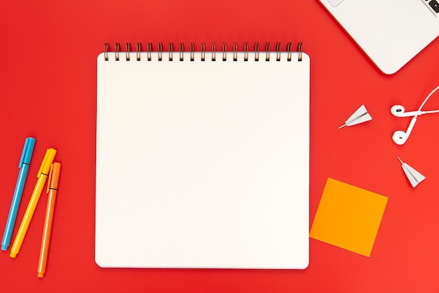 Top view arrangement of desk elements on red background