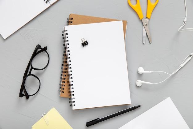 Top view arrangement of desk elements with empty notebook