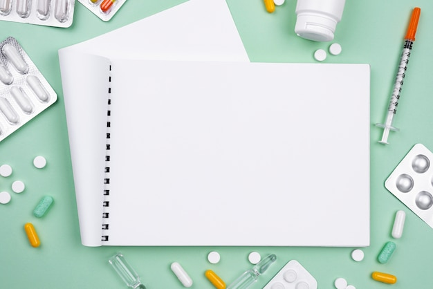 Top view arrangement of medical objects with empty notebook