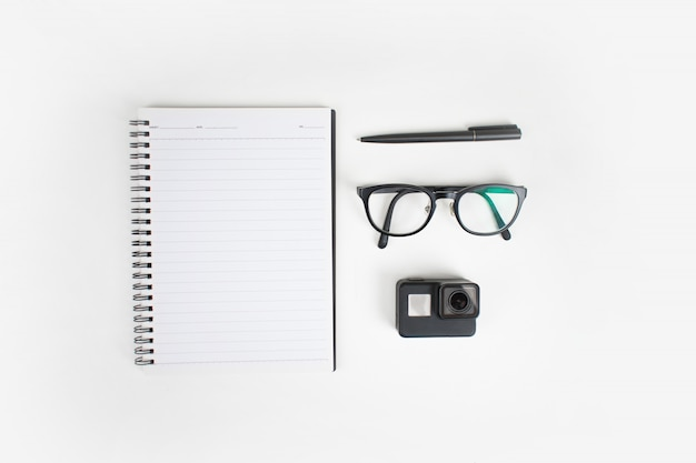 Top view of arrangement of notebooks, glasses, pen and camera.