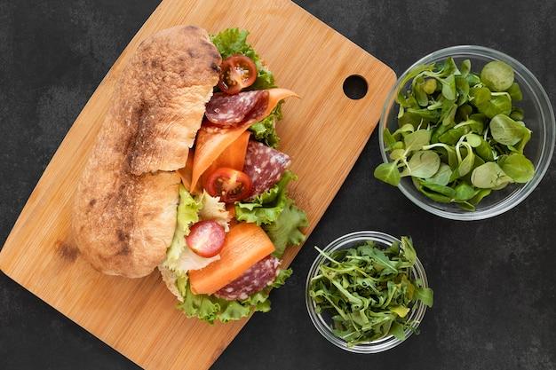 Вид сверху расположение вкусных бутербродов на деревянной доске