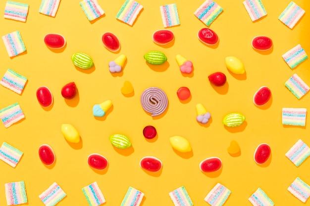 黄色の背景に異なる色のキャンディーの平面図配置