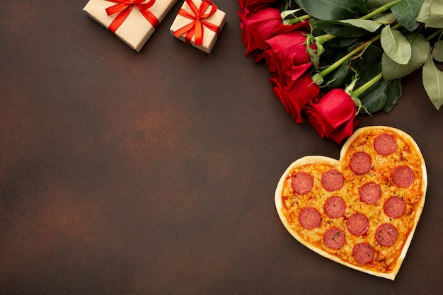 Top view arrangement for valentines day with heart shaped pizza and copy space