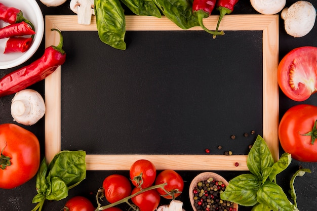 Top view arrangement of vegetables with empty blackboard