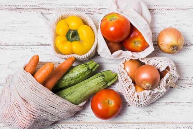 Top view arrangement of vegetables on wooden background
