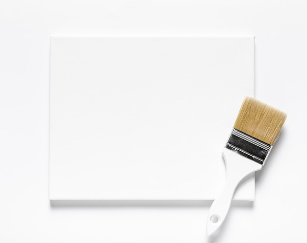 Top view arrangement with canvas and brush on white background