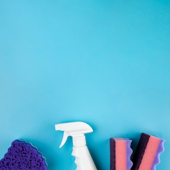 Top view arrangement with cleaning products on blue background
