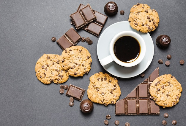 Top view arrangement with cookies, chocolate candies and coffee