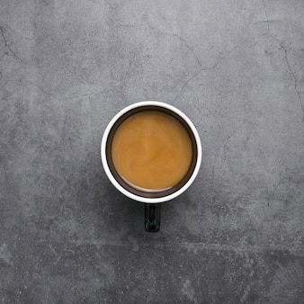 Top view arrangement with cup of coffee on stucco background