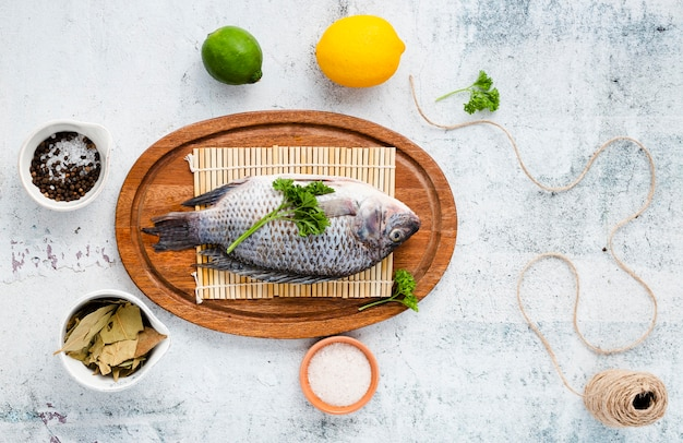 Top view arrangement with delicious fish on wooden plate
