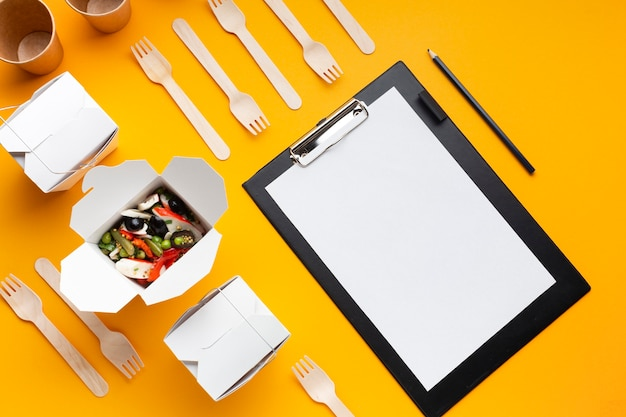 Top view arrangement with food and clipboard