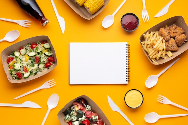 Top view arrangement with food, tableware and notebook