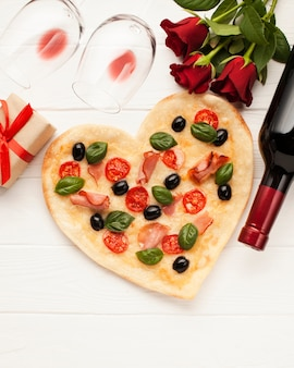 Top view arrangement with heart shaped pizza