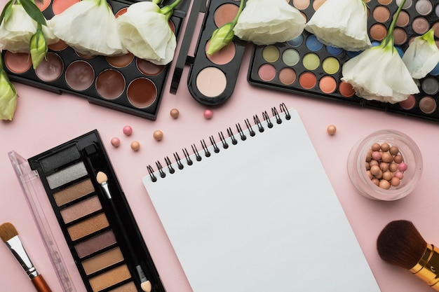 Top view arrangement with make-up items and notebook