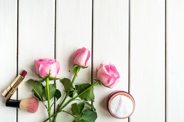 흰색 나무 배경에 메이크업, 장미와 복사 공간 상위 뷰 배열