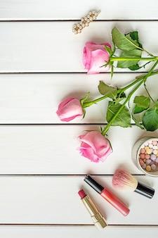 메이크업, 장미, 머리핀 및 흰색 나무 바탕에 복사 공간 상위 뷰 배열. 여성의 날, 아름다움과 여성 성 개념.
