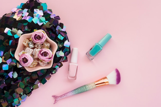 Top view arrangement with nail polish and make-up brush