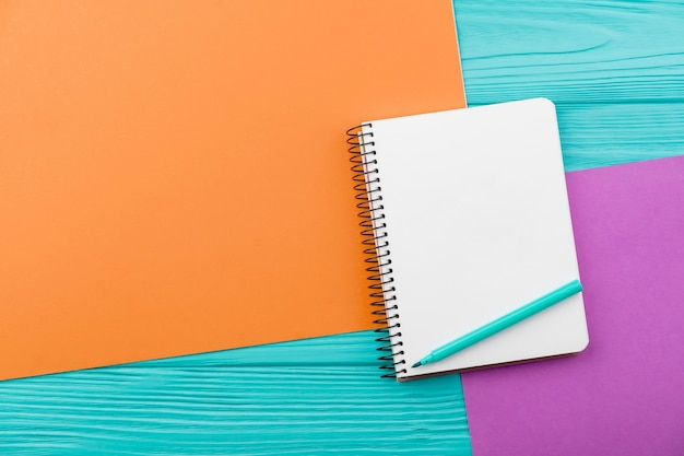 Top view arrangement with notebook on colorful background