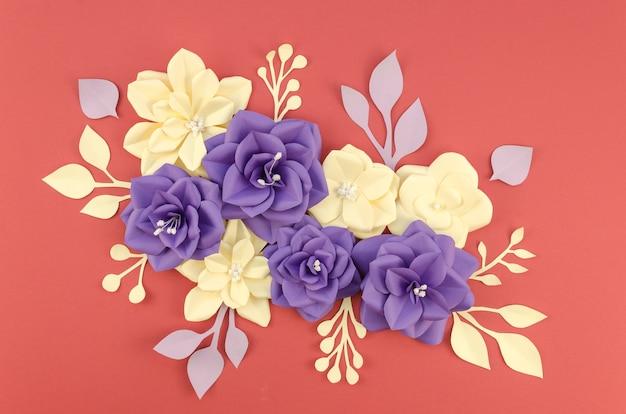 Вид сверху композиция с бумажными цветами и красным фоном