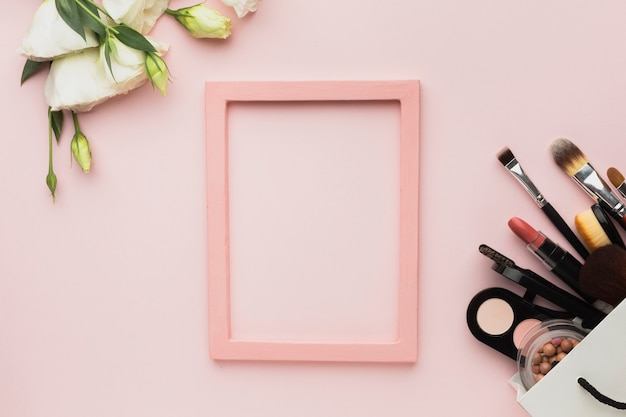 Top view arrangement with pink frame and make-up products