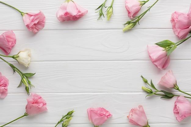 木製の背景にピンクのバラでトップビューの配置