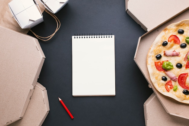Top view arrangement with pizza boxes and notebook