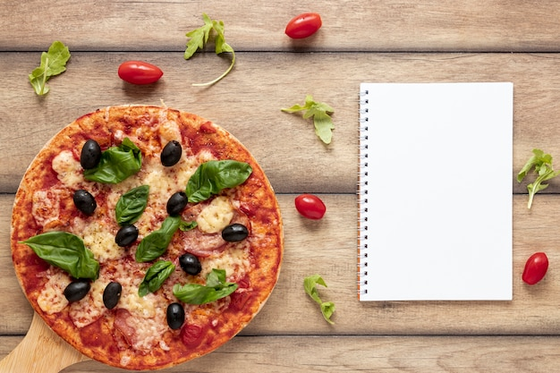 Top view arrangement with pizza and notebook