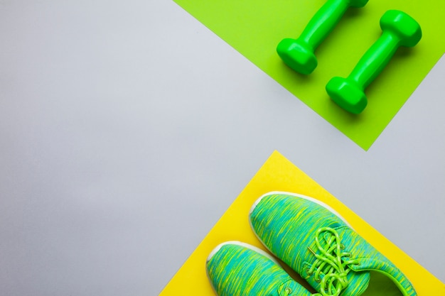 Top view arrangement with running shoes and dumbbells