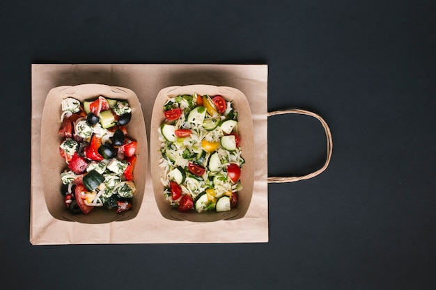 Top view arrangement with salads on paper bag