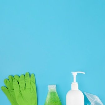 Top view arrangement with soap bottle and green gloves
