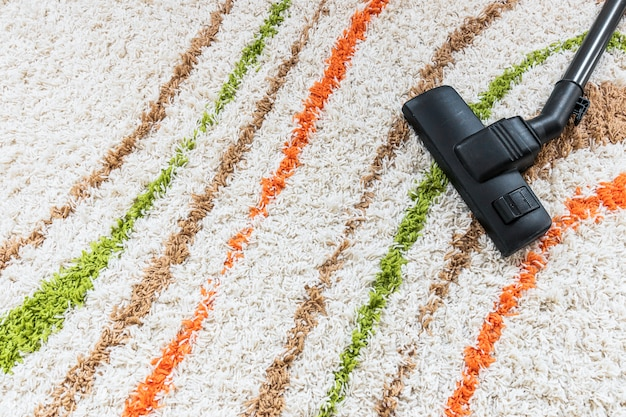 Top view arrangement with vacuum cleaner on carpet